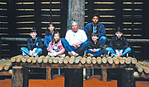 Chief Gilmer Bennett of the Apalachee Indians, along with his son and grandchildren, sit on the chief's bench inside the council house